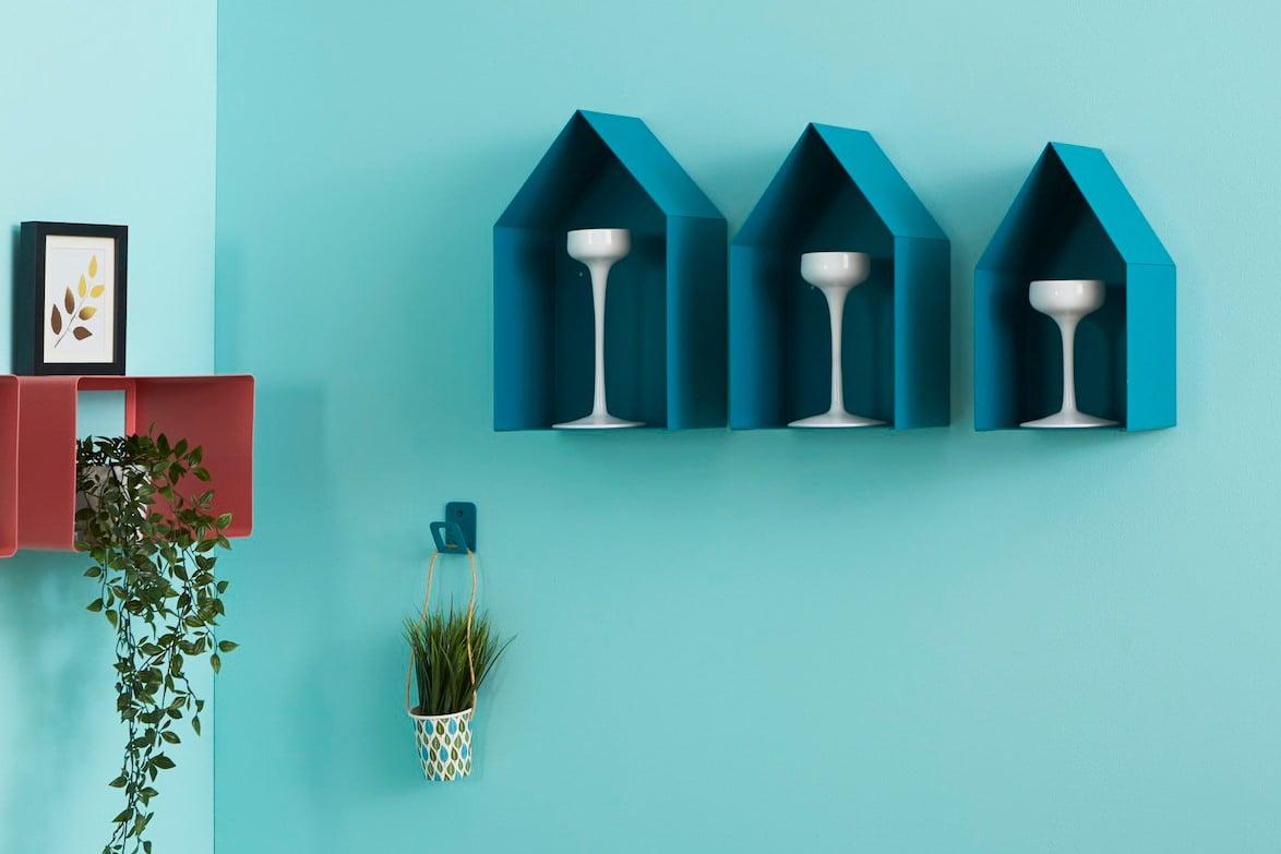 Parete decorata con mensole blu turchese a forma di casetta